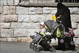 Orthodox woman covers her face with a shawl. Wlaking with her children in Mea Shearim. 27.02.2011. Photography: Miriam Alster, Flash 90