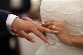 A bride putting a wedding ring on her groom's finger