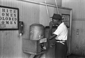 Man drinking from water cooler for ''colored people,'' courtesy of Wikipedia