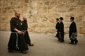 Ultra-Orthodox men pass by Christian Monks in Jerusalem's Old City.  Credit Miriam Alister, Flash 90