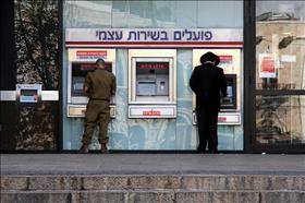 A haredi and a soldier using the bank services. 30.03.2008. Photo: Daniel Dreyfus, Flash 90